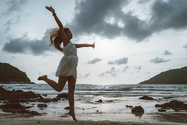 Silhouette girl jump on the beach, twilight, concept black body