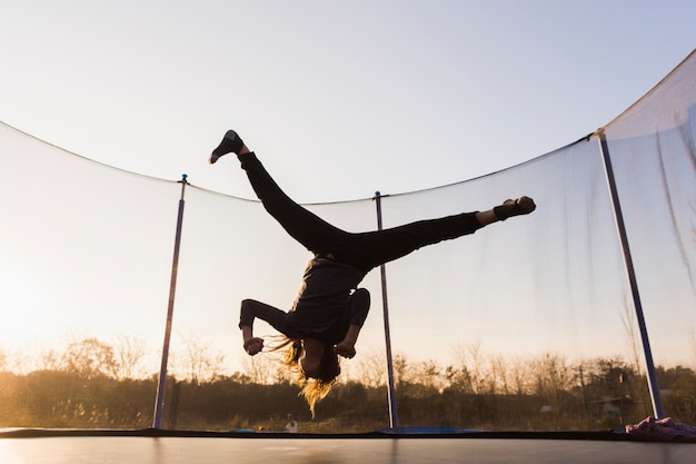 Silhouette of girl jumping on a trampoline doing split