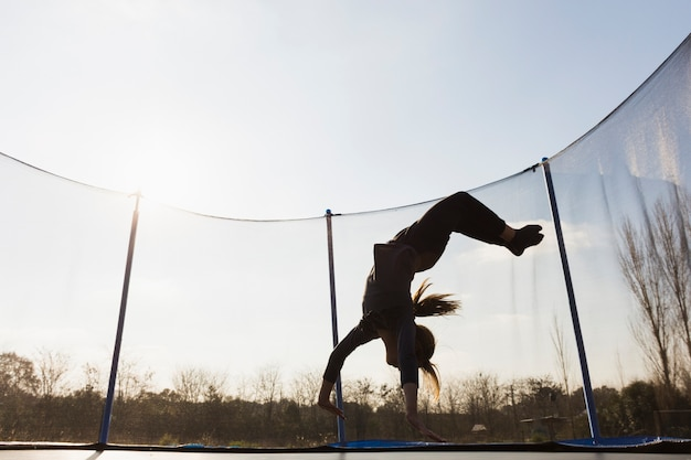 Silhouette of girl jumping upside down on trampoline against the blue sky