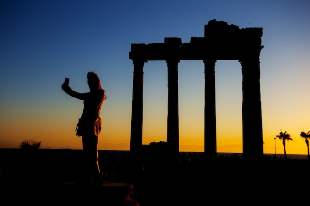 Silhouette of girl making selfie in temple of apollo at sunset