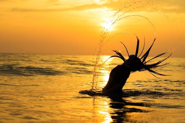 海と夕日に水を再生するシルエットの女の子