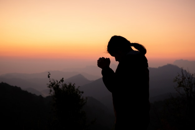 Silhouette of girl praying over beautiful sky background.