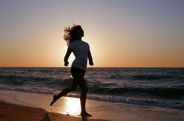 日没の海岸を走るシルエットの女の子