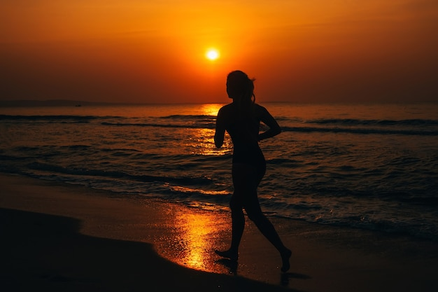 Silhouette of a girl running by the sea on the beach