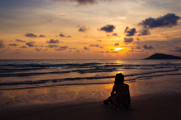 Silhouette of girl sitting on beach with sunset