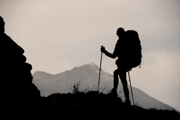 Silhouette girl standing on the rock with hiking backpack and walking sticks