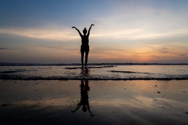 Silhouette of a girl standing in the water with her arms raised and her reflection in the water