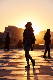 Silhouette of a girl at sunset in winter in casablanca morocco. sun sets behind the girl