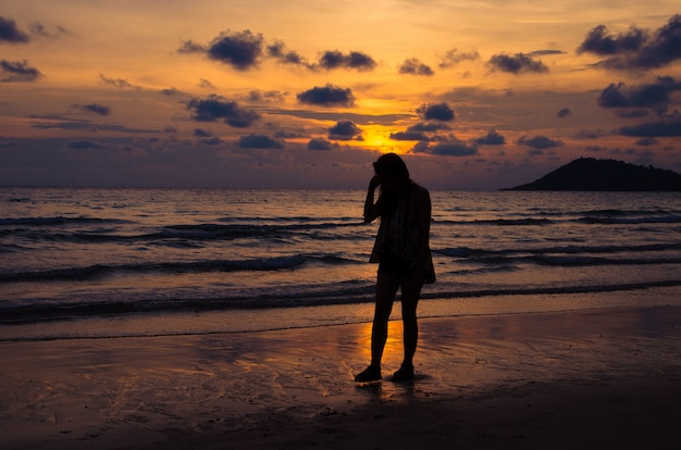Silhouette girl walking on beach with sunset