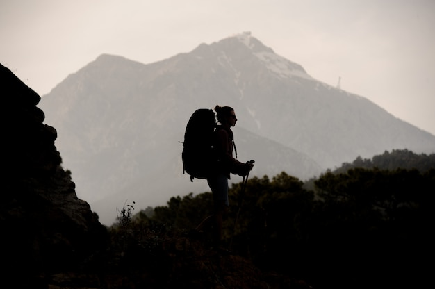 Silhouette girl walking on the rock with hiking backpack and sticks