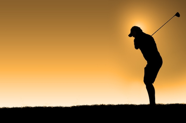 Silhouette of a golfer taking a the first hit of the day with an orange sky background