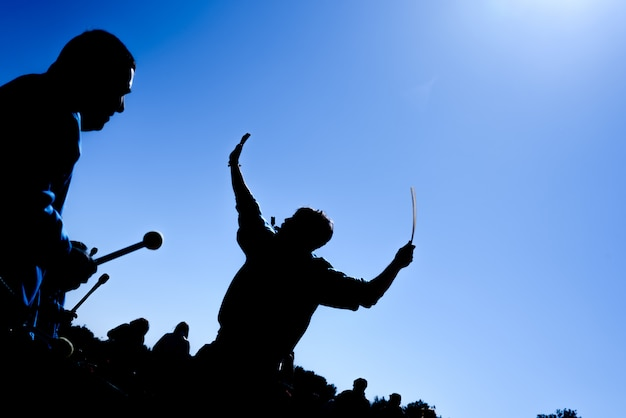 Silhouette of group of drummers in the sun playing.