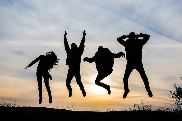 Silhouette of a group of four happy people jumping at sunset