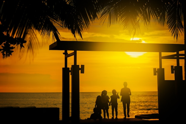 Silhouette, a group of happy children, admiring the beautiful yellow sea sunset. palm leaves. hotel in thailand. summer.