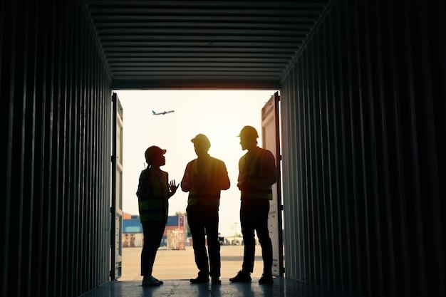 Силуэт группа штатных работников, стоящих и проверяющих коробку контейнеров с грузового корабля для экспорта и импорта