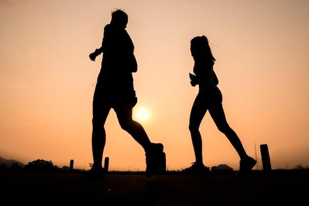 日の出、実行している若い健康的なライフスタイルのシルエットグループ
