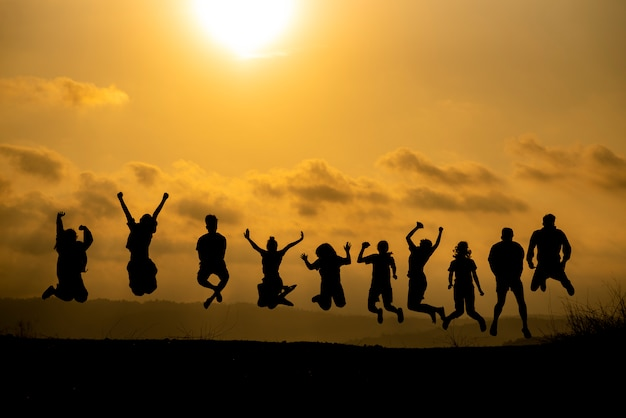 The silhouette of a group of people is celebrating success on the hilltop.