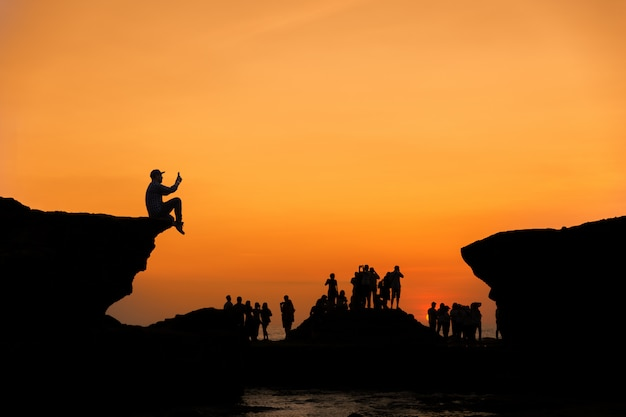 Silhouette group of  people take photo at sunset time between the rock cliff