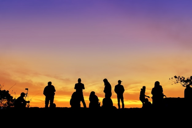 Silhouette of group people travel happy holiday on cliff view their sunrise.
