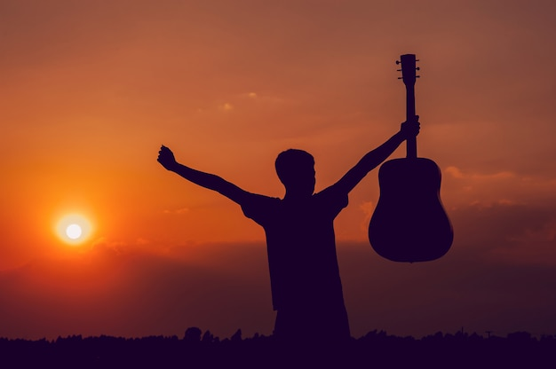 The silhouette of a guitarist who holds a guitar and has a sunset