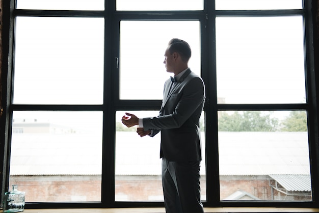 Silhouette of the guy in front of the window. morning of the groom. room in loft style. big windows.