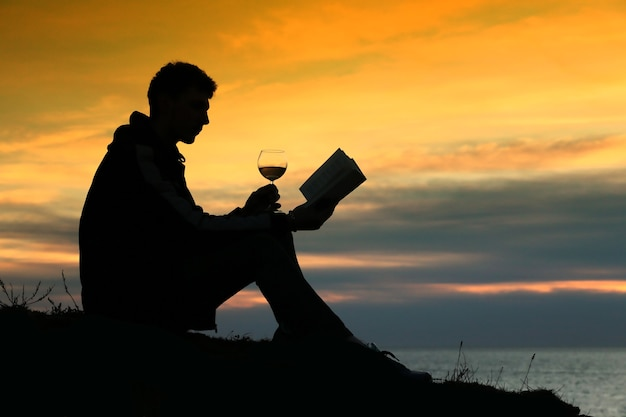 Silhouette guy sitting on breakwater in evening near sea, reads book and drink wine