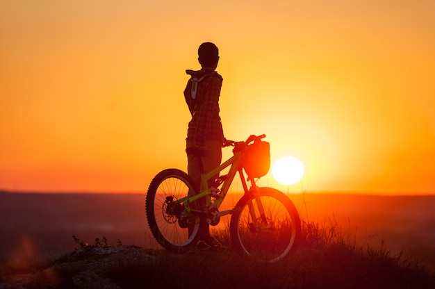 Silhouette of guy with bike at top of mountain on sunset