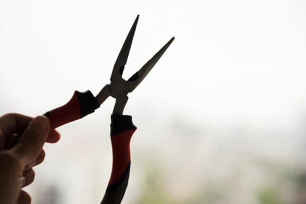 Silhouette of hand holding electric plier