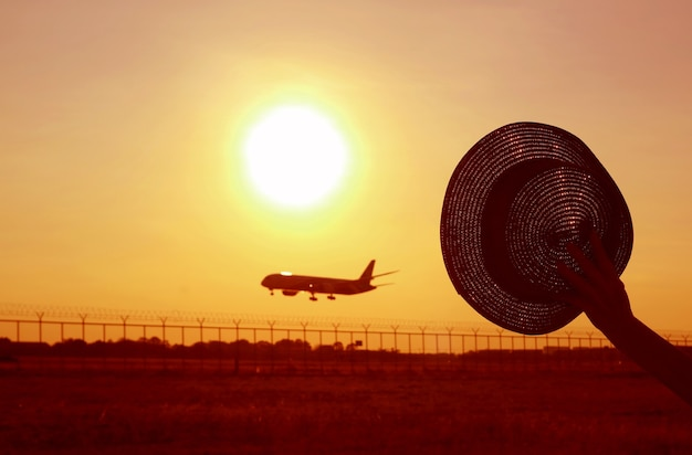 Silhouette of hand holding hat waving to the airplane flying up to the sunrise sky