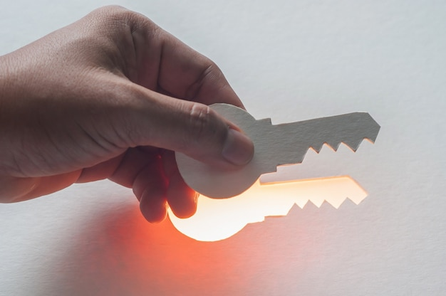 Silhouette hand holding key revealed for success
