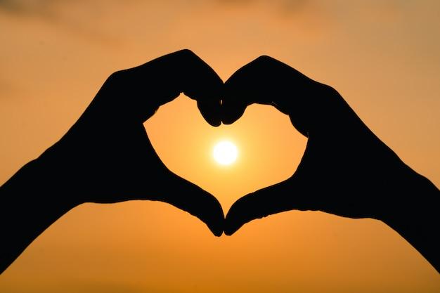 空を背景に日の出とハートの形のシルエットの手。愛の概念。