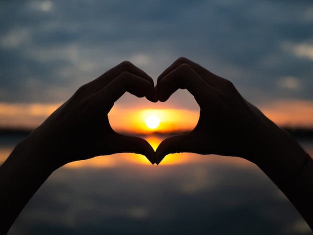 Silhouette hands to be heart shape on sunset background.