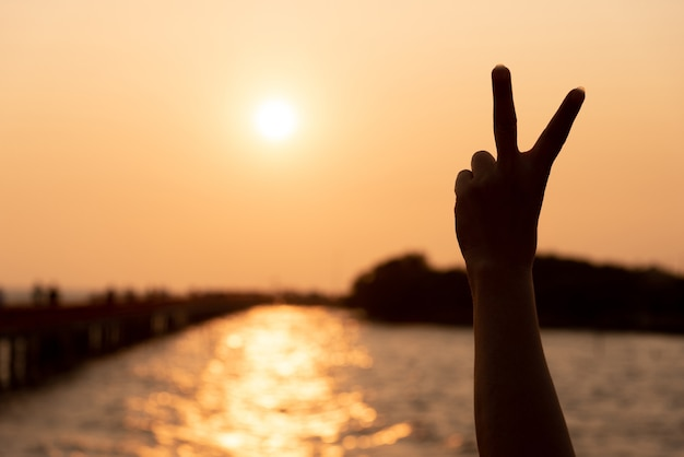 Silhouette of hands holding two fingers on sunset love hope encourage concept, one hand making victory sign at golden hour sunset