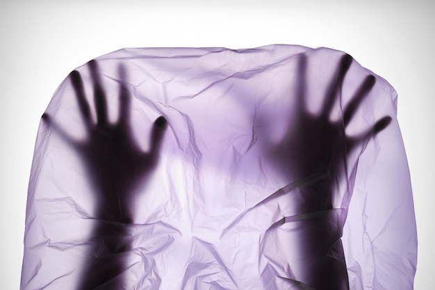 Silhouette of hands in plastic bag