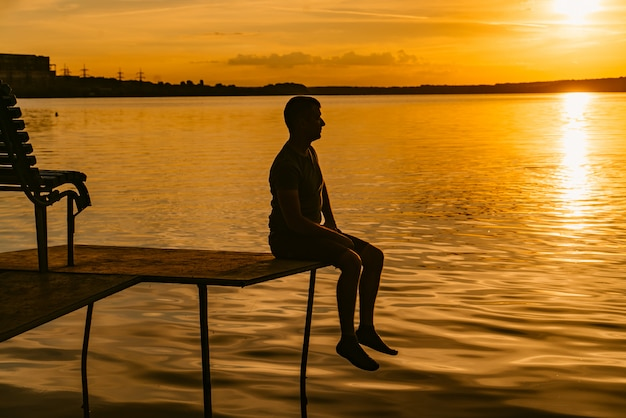 Silhouette of a handsome man sitting on the masonry over the river