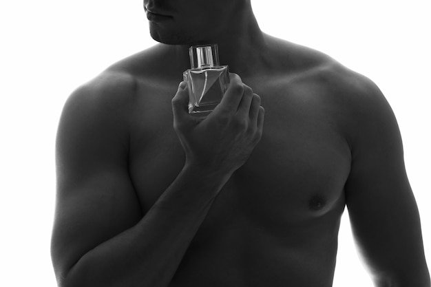Silhouette of handsome young man with bottle of perfume on white surface, closeup