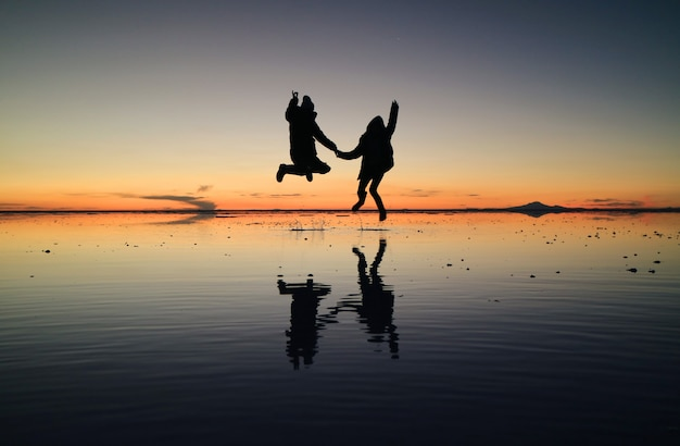 Silhouette of happy couple jumping on the amazing mirror effect of uyuni salt flats against sunset sky