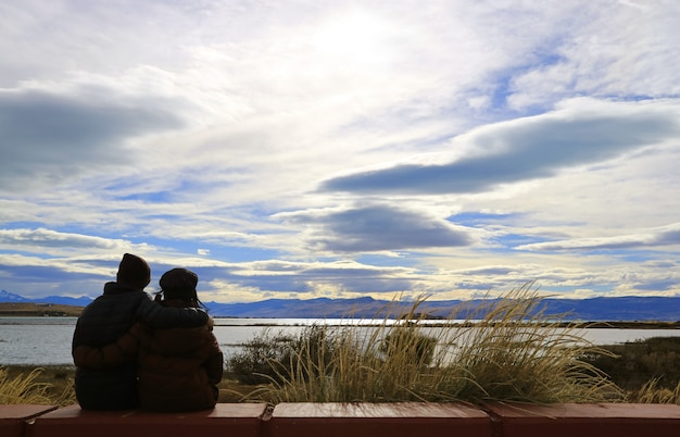 Silhouette of a happy couple relaxing on argentino lake shore in el calafate, patagonia, argentina