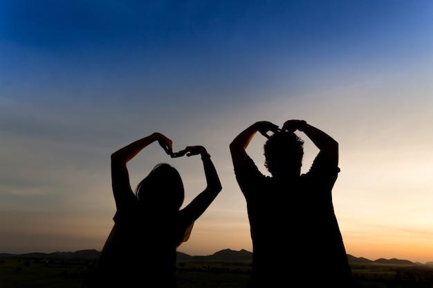 夕暮れの空の背景とシルエット幸せなカップル