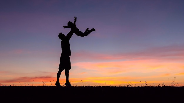 Silhouette of a happy family of father and child  run on meadow