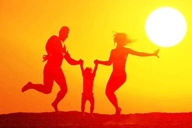 Silhouette of happy family jumping on the beach at sunset