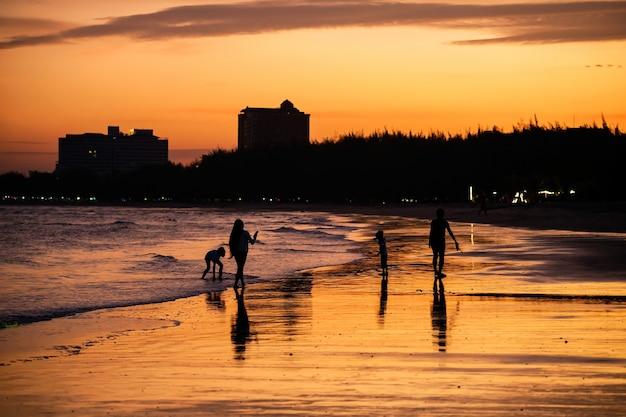 Силуэт счастливая семья на пляже с закатным небом в сумерках в чааме, пхетчабури, таиланд