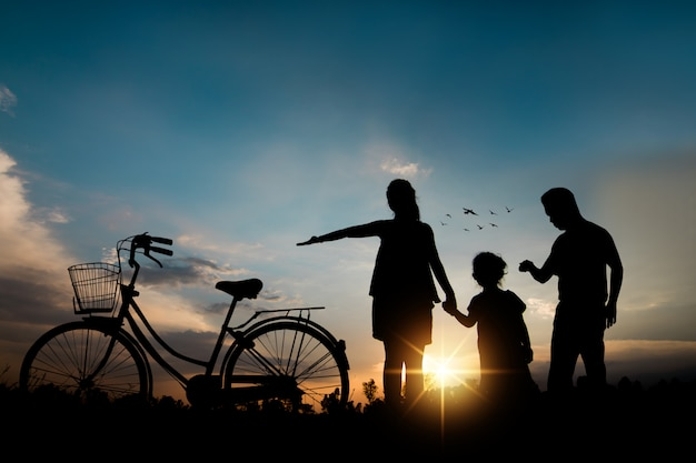 Silhouette of happy family ride bike outside  and walking to filed, freedom and peace concept