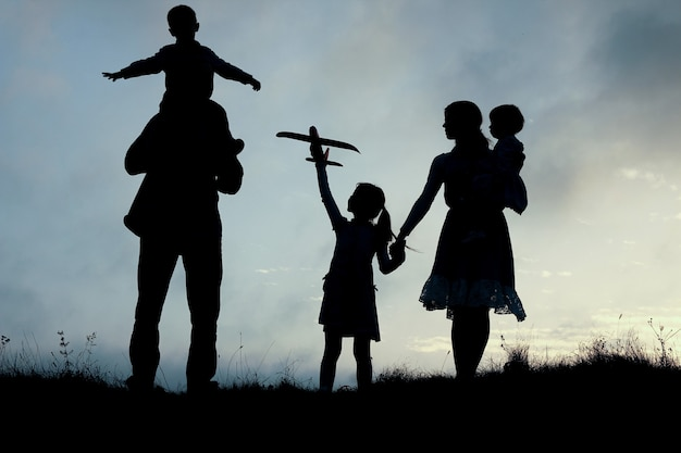 Silhouette of a happy family with children on nature