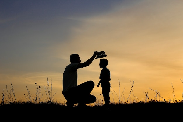 Silhouette of happy father and son play on sunset