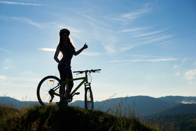 Silhouette of happy female biker with bicycle in the mountains, wearing helmet, showing thumbs up on summer morning against blue sky. outdoor sport activity, lifestyle concept. copy space