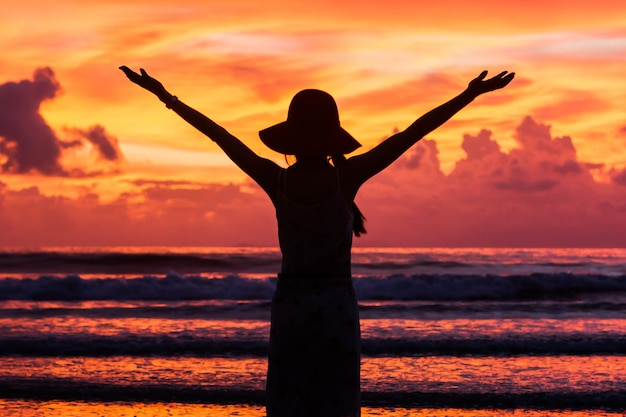 Silhouette happy woman on beautiful sunset sky at tropical beach and sea