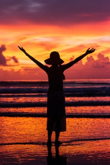 Silhouette happy woman on beautiful sunset sky and tropical beach and sea