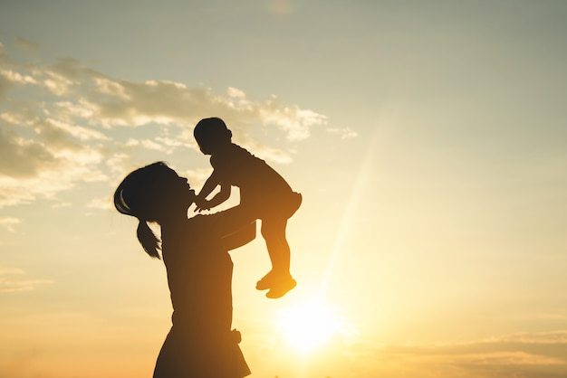 A silhouette of a happy young mother harmonious family outdoors