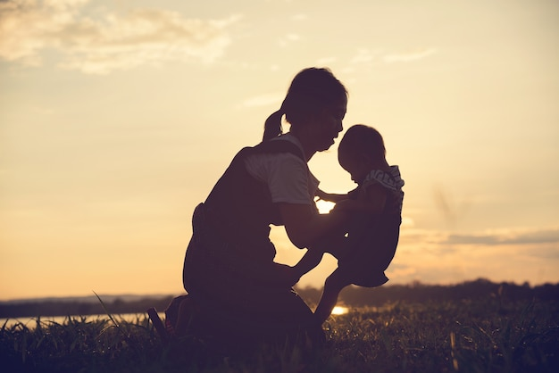 A silhouette of a happy young mother harmonious family outdoors.